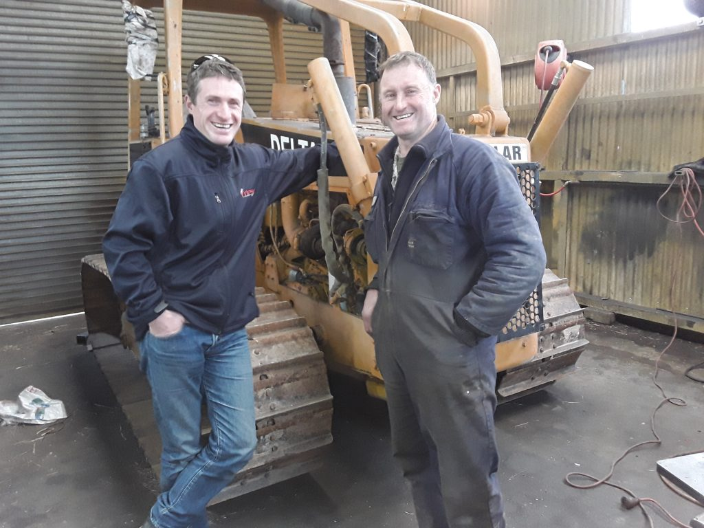 Joe Stringer in front of customer Mike Key from James Engineering with the bulldozer being modified to lay fibre.